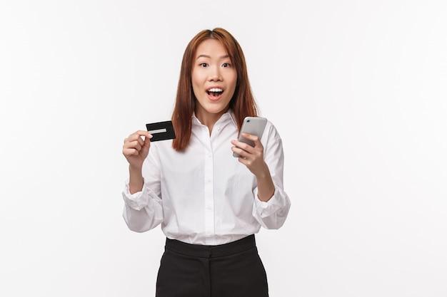 Portret Podekscytowanej Uroczej Azjatyckiej Kobiety W Koszuli I Spódnicy, Trzymającej Telefon Komórkowy I Kartę Kredytową, Składającej Zamówienie Przez Internet, Robiącej Zakupy Online, Korzysta Z Depozytu Bankowego, Rejestruje Konto W Sklepie, Premium Zdjęcia