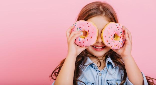 Portret Podekscytowany Radosną Młodą ładną Dziewczyną W Niebieskiej Koszuli, Wyrażając Pozytywne Nastawienie, Zabawy Z Aparatem Z Pączkami Na Oczach Na Białym Tle Na Różowym Tle. Szczęśliwe Dzieciństwo Z Smacznym Deserem. Umieść Tekst Fot Darmowe Zdjęcia