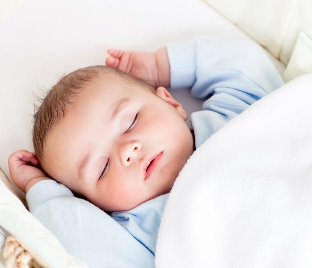 Portret pokojowy dziecka dosypianie w jego kołysce w domu Premium Zdjęcia