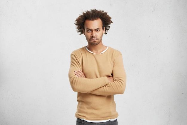 Portret Posępnego, Zrzędliwego Mężczyzny Z Włosami I Kręconymi Włosami, Z Założonymi Rękami Darmowe Zdjęcia