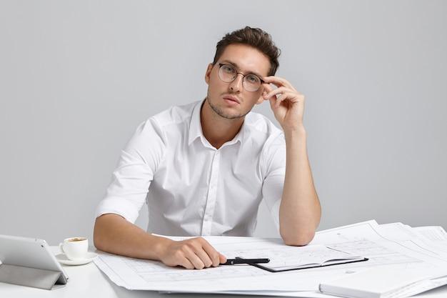 Portret Poważnego, Pewnego Siebie Architekta Pracuje Nad Projektem, Nosi Białą Formalną Koszulę I Okrągłe Okulary Darmowe Zdjęcia