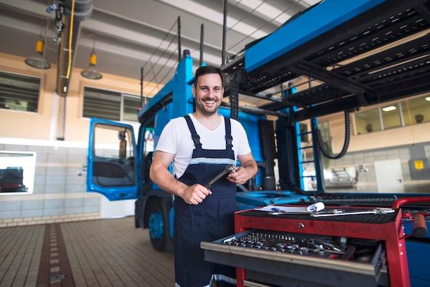 Portret Pozytywny Uśmiechnięty Serwisant Ciężarówki Z Narzędziami Stojący Przy Pojeździe Ciężarówki W Warsztacie Darmowe Zdjęcia