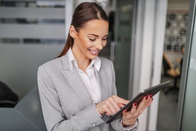 Portret Pracowitej Pozytywnej Kaukaskiej Młodej Bizneswoman Stojącej Wewnątrz Firmy I Za Pomocą Tabletu Do Czytania Wiadomości E-mail. Premium Zdjęcia