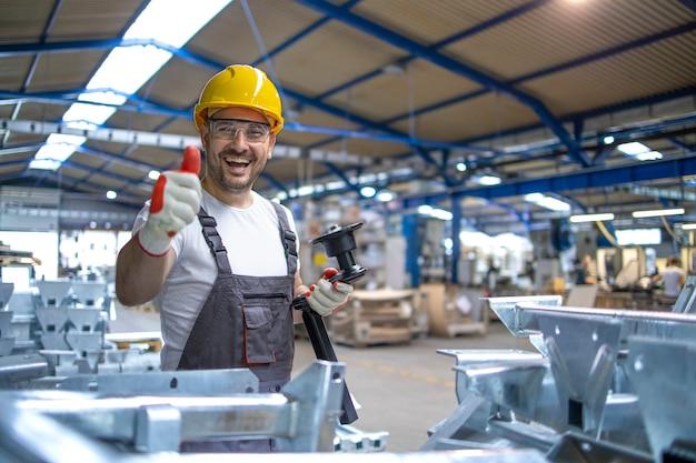 Portret Pracownika Fabryki W Sprzęt Ochronny, Trzymając Kciuki Do Góry W Hali Produkcyjnej Darmowe Zdjęcia