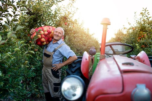 Portret Pracownika Gospodarstwa Worek Pełen Owoców Jabłka Obok Ciągnika W Stylu Retro Darmowe Zdjęcia
