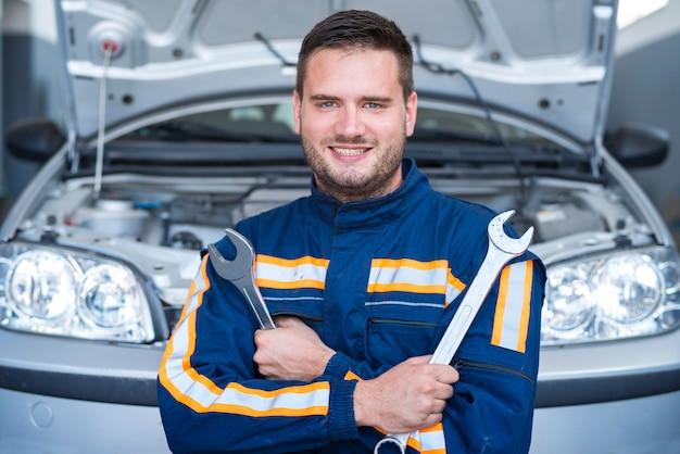 Portret Profesjonalnego Przystojnego Mechanika Samochodowego Trzymającego Klucze Przed Samochodem Z Otwartą Maską Darmowe Zdjęcia