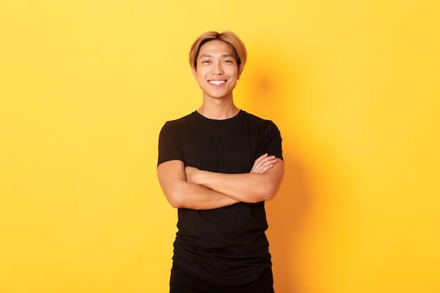 Portret Przekonany Przystojny Azjatycki Mężczyzna Uśmiechnięty Zadowolony, Stojąc Na żółtej ścianie W Czarnych Ubraniach. Darmowe Zdjęcia