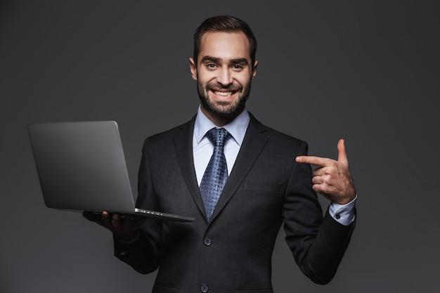 Portret Przekonany, Przystojny Biznesmen Na Sobie Garnitur Odizolowane, Trzymając Laptopa Premium Zdjęcia