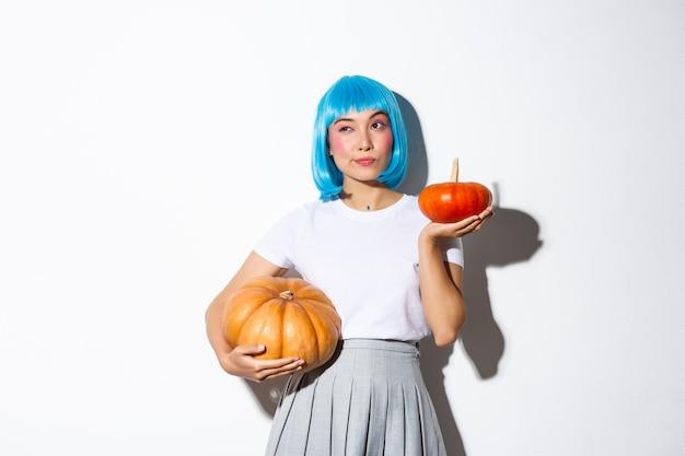Portret Przemyślanej ślicznej Azjatki Odwracającej Wzrok Podczas Dokonywania Wyboru, Trzymającej Dwie Różne Dynie, Dekorującej Przyjęcie Z Okazji Halloween, Noszącej Niebieską Perukę. Darmowe Zdjęcia