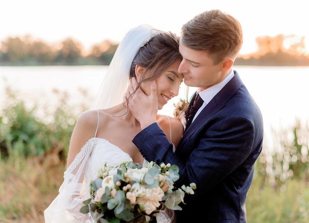 Portret Przetargu ślub Para Blisko Wody Prawie Całuje Z Pięknym ślubnym Bukietem W Rękach Na Ciepłym Wieczór Darmowe Zdjęcia