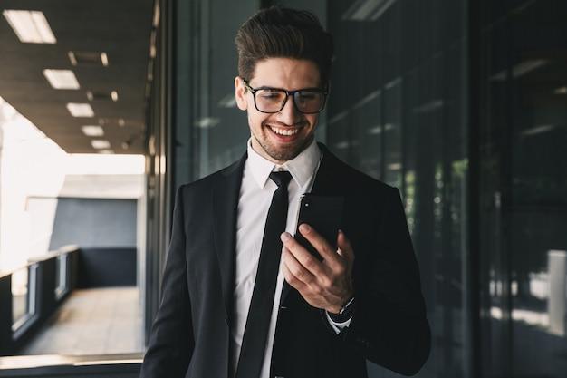 Portret Przystojny Młody Biznesmen Ubrany W Formalny Garnitur Stojący Na Zewnątrz Budynku Ze Szkła I Trzymając Telefon Komórkowy Premium Zdjęcia