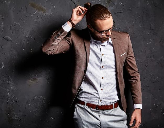 Portret Przystojny Moda Model Hipster Stylowy Biznesmen Biznesmen Ubrany W Elegancki Brązowy Garnitur W Okularach W Pobliżu Ciemnej ściany Darmowe Zdjęcia
