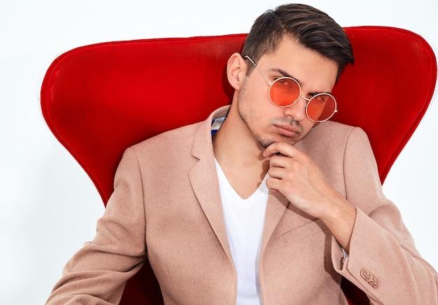 Portret Przystojny Moda Model Stylowy Biznesmen Ubrany W Elegancki Jasnoróżowy Garnitur, Siedząc Na Krześle Czerwony. Metroseksualny Darmowe Zdjęcia