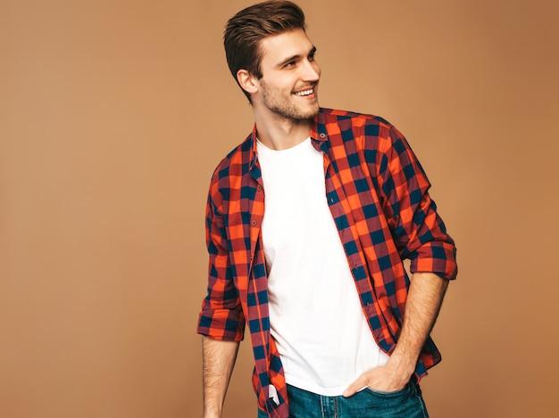 Portret Przystojny Uśmiechnięty Stylowy Młody Model Mężczyzna Ubrany W Czerwoną Kraciastą Koszulę. Moda Mężczyzna Pozowanie Darmowe Zdjęcia