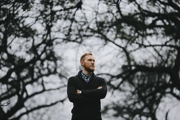 Portret przystojny wysoki mężczyzna stoi outside w gęstej jesieni Darmowe Zdjęcia
