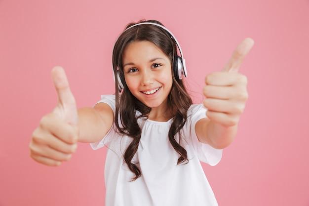 Portret Radosnej Dziewczyny 8-10 W Ubranie Pokazujące Kciuki Do Góry Na Aparat Obiema Rękami Podczas Słuchania Muzyki Przez Słuchawki Bezprzewodowe, Odizolowane Na Różowym Tle Premium Zdjęcia