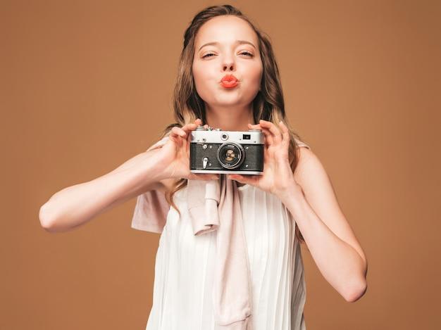 Portret Rozochocona Młoda Kobieta Bierze Fotografię Z Inspiracją I Jest Ubranym Biel Suknię. Dziewczyna Trzyma Aparat Retro. Pozowanie Modelu. Pocałunek Darmowe Zdjęcia