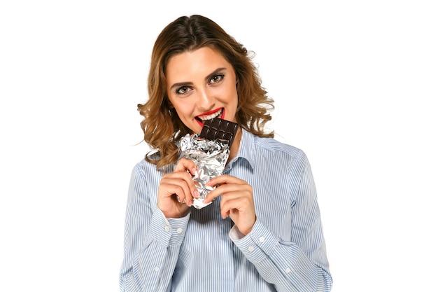 Portret rozochocona młoda kobieta je smakowitą ciemną czekoladę zawijającą w folii Darmowe Zdjęcia
