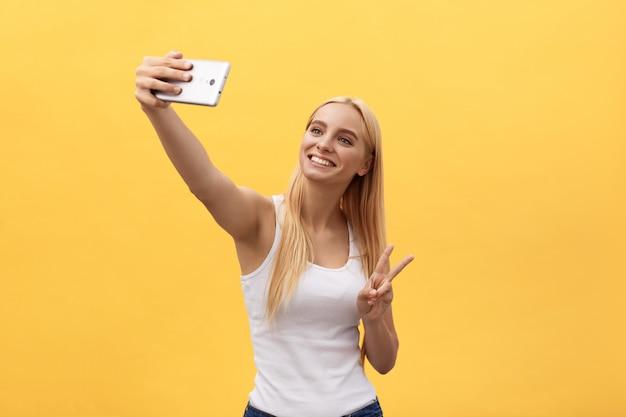 Portret Rozochocona Uśmiechnięta Kobieta W Białej Koszula Bierze Selfie Odizolowywającego Na żółtym Tle Premium Zdjęcia