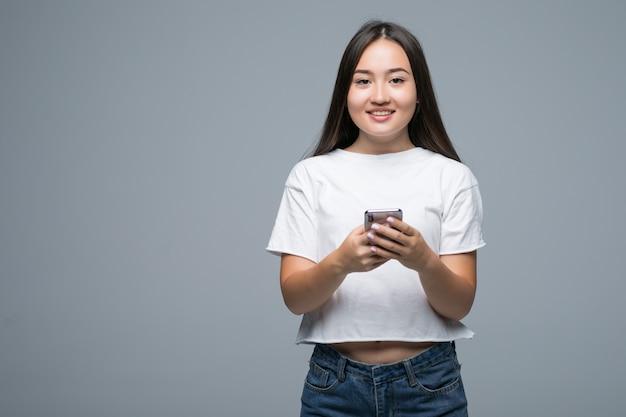 Portret Rozochocony Azjatykci Kobiety Mienia Telefon Komórkowy I Patrzeć Kamerę Nad Szarym Tłem Darmowe Zdjęcia