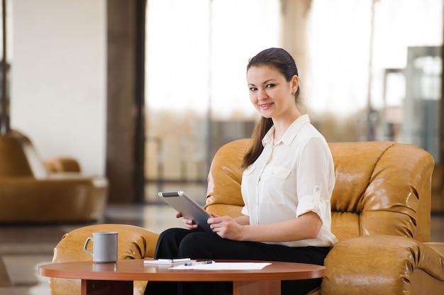 Portret ruchliwie biznesowej kobiety działanie i obsiadanie przy kanapą Premium Zdjęcia
