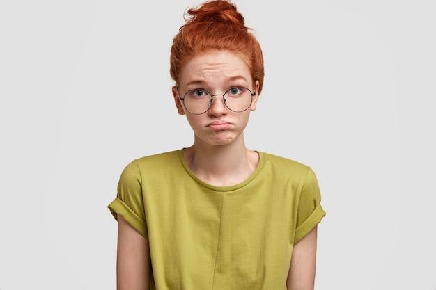 Portret Rudej Kobiety Zaciska Dolną Wargę Z Niezadowoleniem, Czuje Się Urażona, Gdy Słyszy Negatywne Komentarze, Nosi Dorywczo Jasną Koszulkę Darmowe Zdjęcia