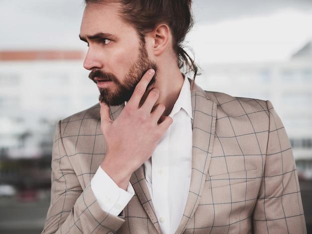 Portret Seksowny Przystojny Moda Mężczyzna Model Mężczyzna Ubrany W Elegancki Beżowy Kratkę Garnitur Pozowanie Na Tle Ulicy Darmowe Zdjęcia