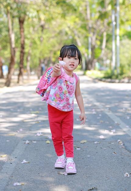 Portret śliczna Mała Dziewczynka W Jawnym Parku Z Mienie Kwiatem Dla Ciebie. Premium Zdjęcia