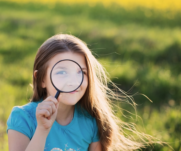 Portret śliczna Młoda Dziewczyna Patrzeje Przez Powiększać - Szkło Premium Zdjęcia
