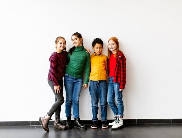 Portret śliczne Małe Dzieci W Dżinsach, Uśmiechając Się, Stojąc Przed Białą ścianą Premium Zdjęcia
