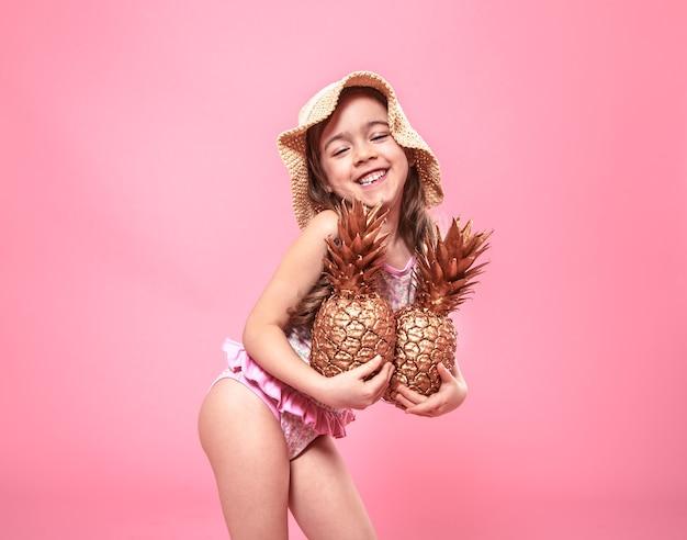 Portret ślicznej Dziewczynki W Letnim Kapeluszu, Trzymającego Dwa Ananasy Pomalowane Na Złoto, Pojęcie Lata I Kreatywności Darmowe Zdjęcia