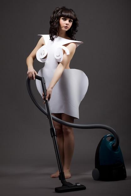 Portret ślicznej Młodej Szczupłej Dziewczyny W Sukienkach Origami Odkurzających Odkurzaczem Na Szarym Tle Premium Zdjęcia