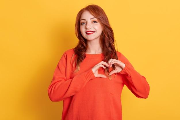 Portret ślicznej Rudowłosej Modelki Robi Gest Serca, Demonstruje Znak Miłości, Ma Szczęśliwy Wyraz Twarzy, Ubrana W Pomarańczowy Sweter, Pozuje Na żółtym Tle. Premium Zdjęcia