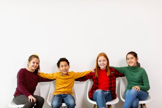 Portret Słodkie Małe Dzieci W Dżinsach Siedzi Na Krzesłach Pod Białą ścianą Premium Zdjęcia