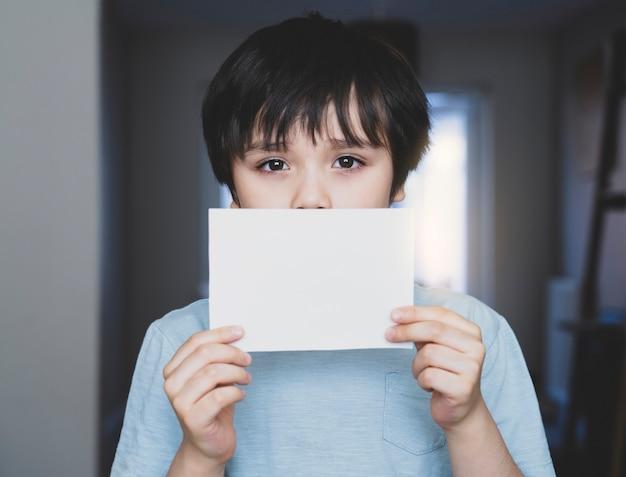 Portret Smutnego Dzieciaka Mienia Pusty Biały Papier, Osamotniony Chłopiec Pokazuje Białego Papier Bez Słów Premium Zdjęcia