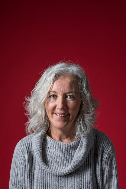 Portret Starsza Kobieta Z Krótkim Szarym Włosy Przeciw Czerwonemu Tłu Darmowe Zdjęcia