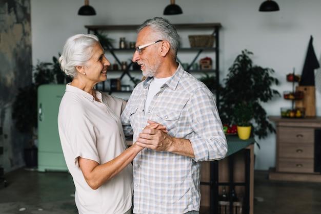 Portret starsza para tanczy wpólnie w kuchni Darmowe Zdjęcia