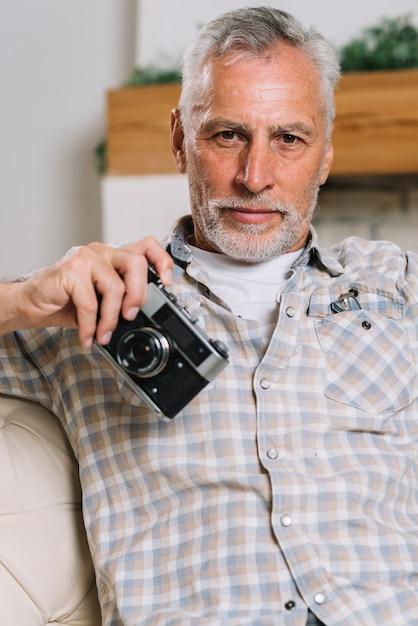 Portret starszego mężczyzna mienia kamera w ręce patrzeje kamerę Darmowe Zdjęcia