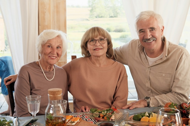 Portret Starszych Ludzi Uśmiecha Się Siedząc Przy Stole W Domu Premium Zdjęcia
