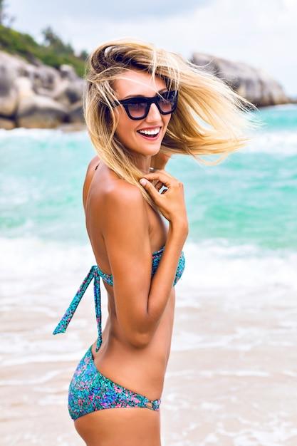 Portret Styl życia Na Zewnątrz Mody Iść Młoda Seksowna Blondynka Z Dopasowanym Opalonym Ciałem, Ubrana W Stylowe Bikini I Okulary Przeciwsłoneczne, Bawiąc Się Na Tropikalnej Plaży Na Wyspie. Skacząc, Uśmiechając Się I Krzycząc. Darmowe Zdjęcia