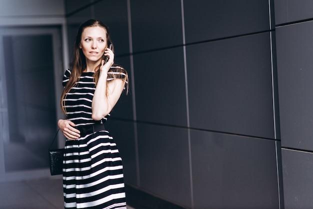 Portret Stylowe Młoda Kobieta Spaceru W Nowoczesnym Mieście I Talsing Na Telefon Komórkowy Premium Zdjęcia