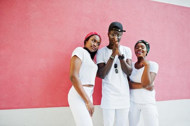 Portret Stylowego Amerykanina Afrykańskiego Pochodzenia Mężczyzna Modlenia Ręki Z Dwoma Dziewczynami, Jest Ubranym Na Biel Ubraniach, Przeciw Menchii ścianie. Moda Uliczna Młodych Czarnych Ludzi. Premium Zdjęcia