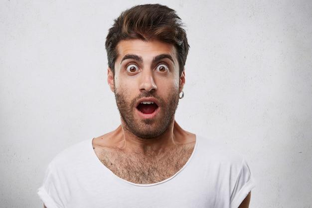 Portret Stylowego Brodatego Faceta O Modnej Fryzurze W Kolczyku I Białej Koszulce, Patrząc Oczami, Wyskoczył I Otworzył Usta Z Szokiem I Przestraszeniem. Darmowe Zdjęcia
