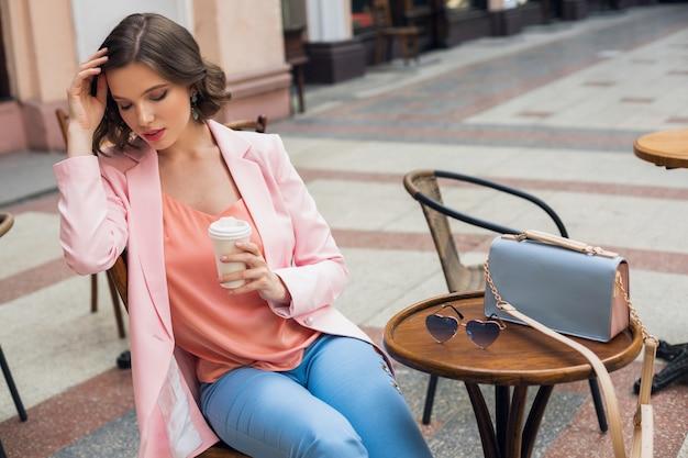 Portret Stylowej Romantycznej Kobiety Siedzącej W Kawiarni Pijącej Kawę, Ubrana W Różowe I Niebieskie Kolory W Odzieży, Trend Wiosenno-letni, Modne Okulary Przeciwsłoneczne I Torebka Darmowe Zdjęcia