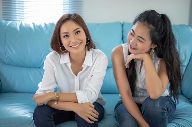 Portret stylu życia azjatyckie kobiety najlepszych przyjaciół - uśmiecha się szczęśliwy na kanapie w salonie Premium Zdjęcia