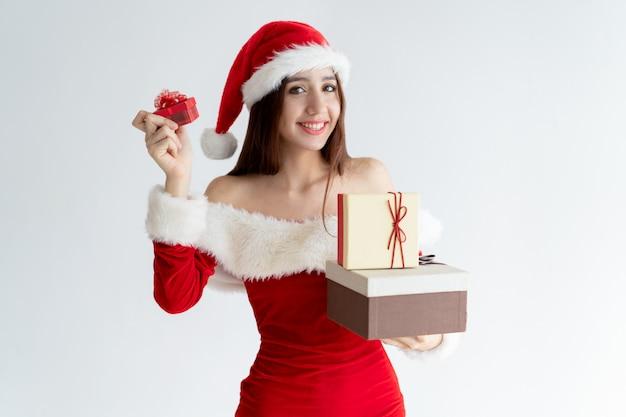 Portret szczęśliwa dziewczyna w santa pomagiera prezenta smokingowych pokazuje pudełkach Darmowe Zdjęcia