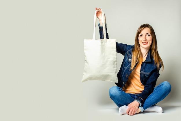 Portret Szczęśliwa Młoda Kobieta Siedzi Ze Skrzyżowanymi Nogami, Trzymając Lnianą Torbę Z Zakupami Na Jasnym Tle Premium Zdjęcia