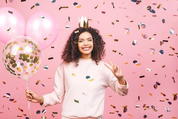 Portret Szczęśliwa Młoda Kobieta Z Różową Koszulką Z Kolorowych Balonów I Konfetti Premium Zdjęcia