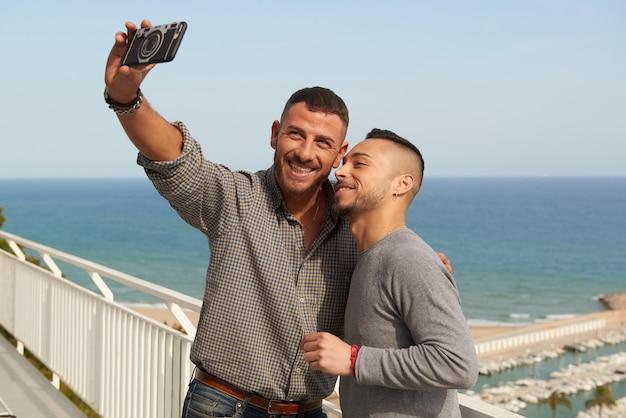 Portret Szczęśliwa Para Gejów Na Zewnątrz Co Selfie Z Telefonu Komórkowego Premium Zdjęcia