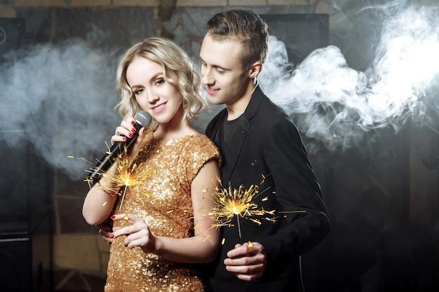 Portret szczęśliwa potomstwo para śpiewa z mikrofonem z sparklers. Premium Zdjęcia